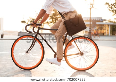 Cropped picture of handsome young african man early morning with bicycle walking outdoors. #702007555