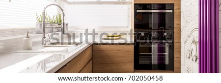 Designed kitchen with white glossy countertop and stainless steel faucet in front of violet heater