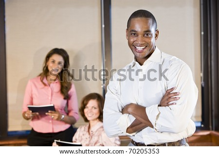 Diversity in workplace - African American office worker with female colleagues, focus on man #70205353