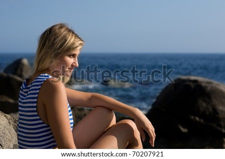 Attractive thoughtful girl on a beautiful rocky beach by the sea. #70207921