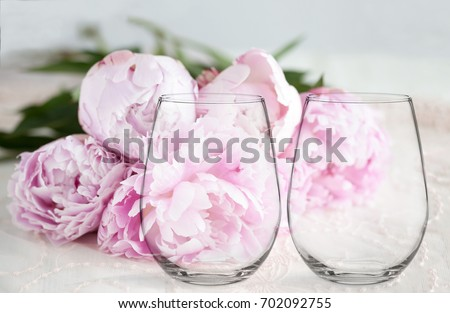 Floral mock-up of 2 stemless wine glasses, in front of a bunch of peonies, perfect for businesses who sell decals, vinyl stickers, just overlay your design