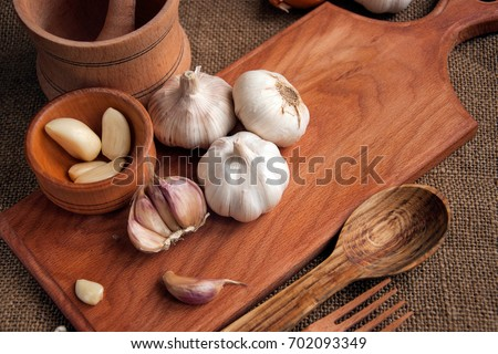 Garlic. sliced garlic, garlic clove, garlic bulb in wooden bowl place on chopping block on vintage wooden background. Place for text,  copy space Concept of healthy food. Top view #702093349