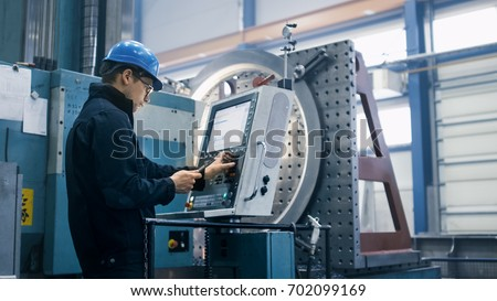 Factory worker is programming a CNC milling machine with a tablet computer. #702099169