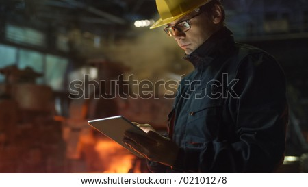 Engineer in Glasses using Tablet PC in Foundry. Industrial Environment. #702101278