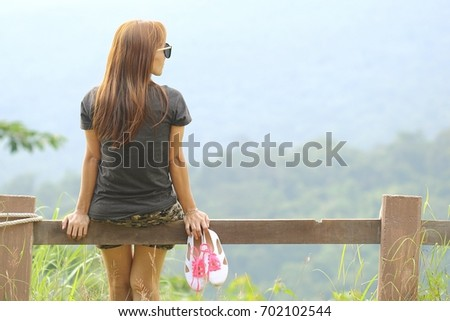 Young woman sitting mountain view Amidst the beautiful nature #702102544