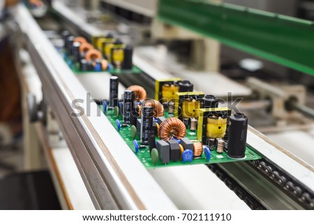 Manual insertion of electronic components on printing circuit board assembly before wave soldering. The image taken in a electronic production plat on a conveyor belt.   Royalty-Free Stock Photo #702111910
