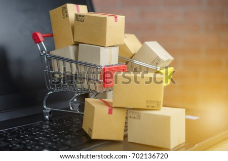 Many boxes in a trolley on a laptop keyboard,on brick background.concept online shopping. #702136720