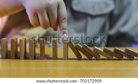 Boys use his hand to stop effect of dominoes. #702172909