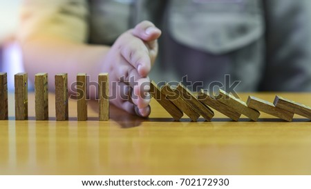 Boys use his hand to stop effect of dominoes. #702172930