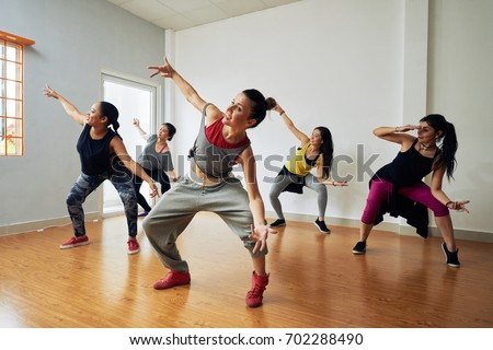 Group of energetic hip-hop dancers focused on training while gathered together in spacious dance hall Royalty-Free Stock Photo #702288490
