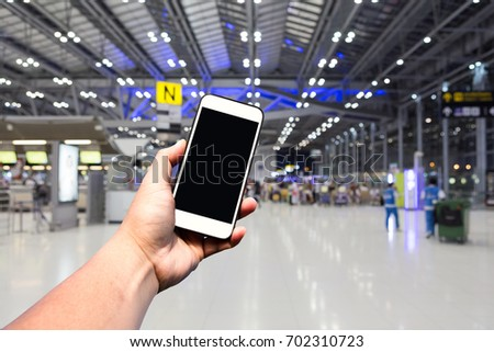 Hand hold Modern smartphone with blank screen in international airport. Background with copy space. #702310723