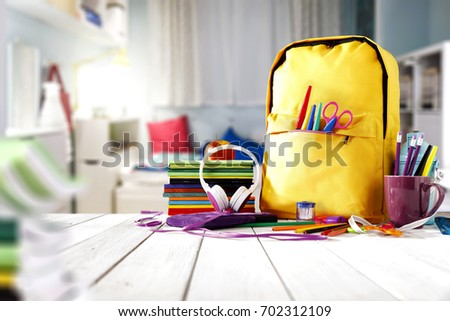 School supplies on a wooden table in a warm interior Royalty-Free Stock Photo #702312109