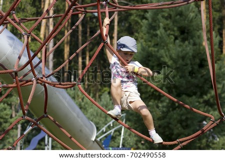 Active young girl climbing the spider web playground activity in summer. #702490558