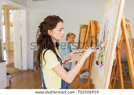 art school, creativity and people concept - student girl or young woman artist with easel, palette and paint brush painting still life picture at studio #702506959