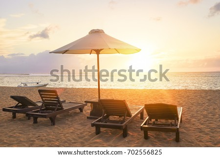 Stunning beautiful sunlight beach with relaxing scenery on a beach. Famous travel destination in Sanur, Bali, Indonesia. #702556825