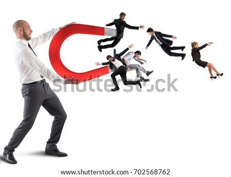 Businessman attracts people with a big magnet Royalty-Free Stock Photo #702568762