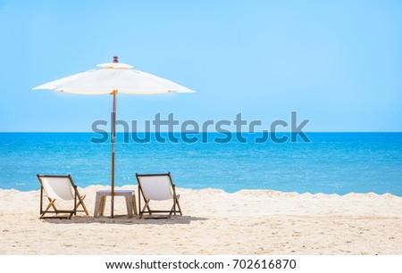 Beach chair with umbrella in blue sky on tropical beach. #702616870