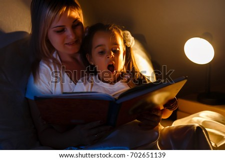 Mother and Daughter storytelling sitting on the bed, Mother reads, daughter yawns #702651139