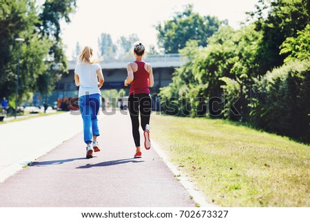 Two young woman are jogging in the morning. #702673327