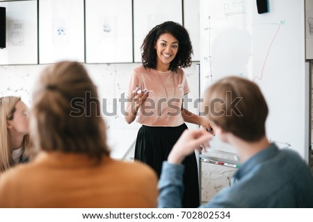 Cheerful African American lady with dark curly hair standing near board and happily looking at her colleagues in office. Young beautiful business woman giving presentation to coworkers during meeting #702802534