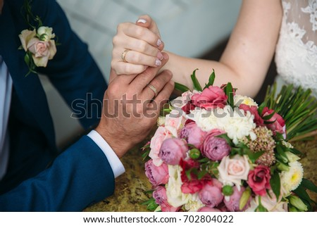 Closeup groom and bride are holding hands at wedding day and show rings. Concept of love family #702804022