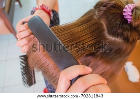 Closeup Woman straightening hair with straightener  with long red hair.  #702811843