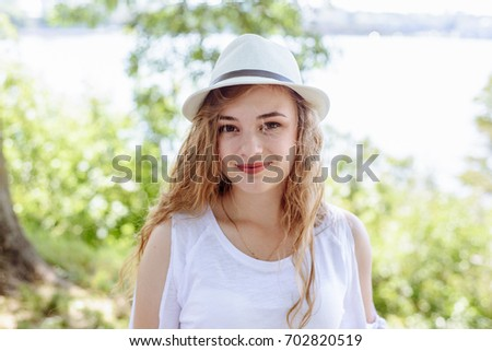 Portrait of a beautiful young blonde girl in hat, outdoors #702820519