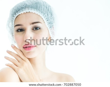 Beautiful woman face closeup portrait hands on skin, Young woman wearing bath cap or bonnet, Beauty Makeup. Closeup Of Beautiful Smiling Woman Touching Soft Smooth Facial Skin, Age 20-30 years.  #702887050