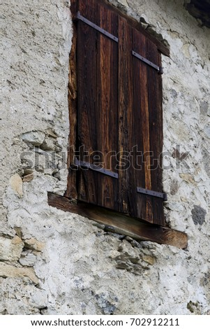 Rustic old wooden shutter on a continental building with flaking rendered stone walls #702912211