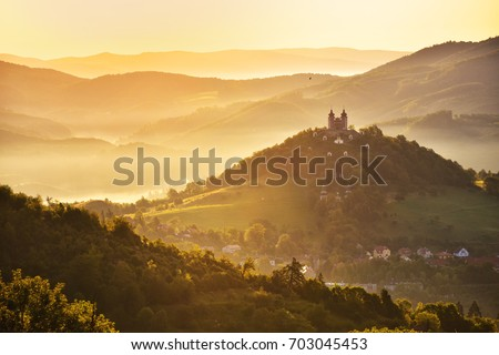 Romantic morning scenery - church with two towers on the top of the hill in beautiful warm summer morning light. Fairy tail photo with copy space. Banska Stiavnica, Slovakia, Unesco