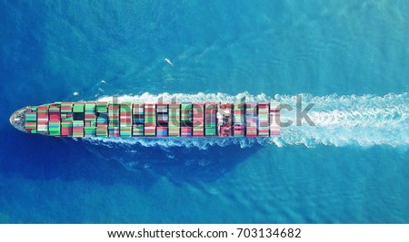 a Large container ship is leaving the port full loaded with containers and cargo - aerial - top down view #703134682
