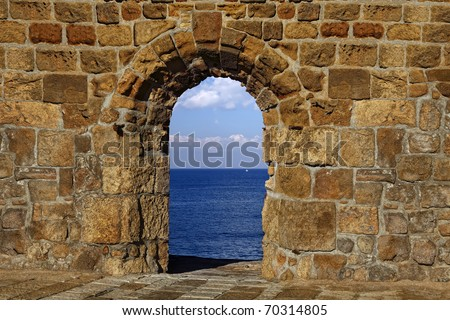 View on a lonely white sail in the dark blue sea through a window in an old fortification #70314805