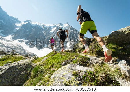 Trail running adventure in the Alps towards the mountains Royalty-Free Stock Photo #703189510