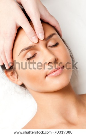 pretty woman receiving face massage, closeup photo