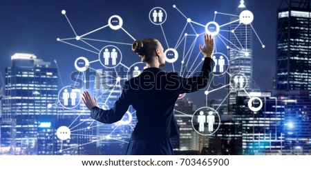Back view of businesswoman against night cityscape working with social connection media concept #703465900