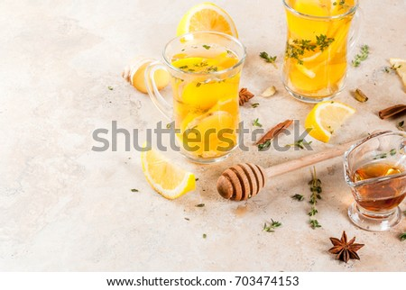 Fall and winter traditional drinks. Warming hot tea with lemon, ginger, spices (anise, cinnamon) and herbs (thyme), copy space #703474153