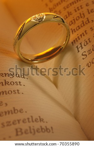 golden ring makes heart shaped shadow in book,hungarian text #70355890
