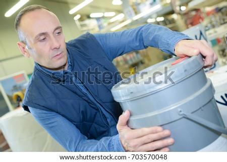 man holding paint bucket #703570048