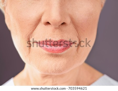 Closeup view of beautiful elderly woman on gray background #703594621