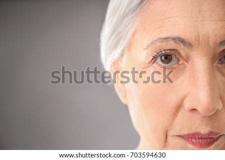Closeup view of beautiful elderly woman on gray background #703594630