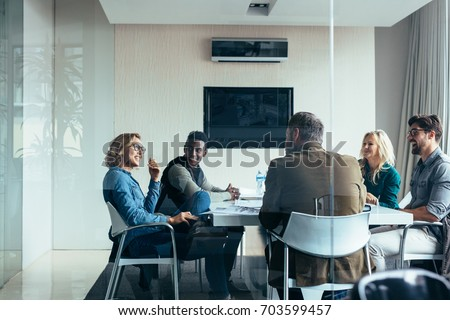 Female manager leads brainstorming meeting in design office. Businesswoman in meeting with colleagues in conference room. Royalty-Free Stock Photo #703599457
