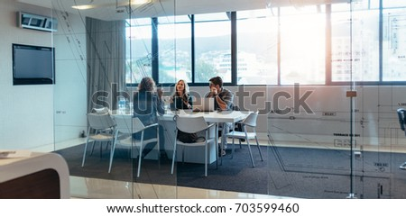 Three designers discussing about new project in meeting hall. Group of executives meeting in boardroom. Royalty-Free Stock Photo #703599460