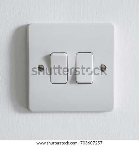 Generic white UK light switch with two buttons, screwed to a painted wall.  #703607257