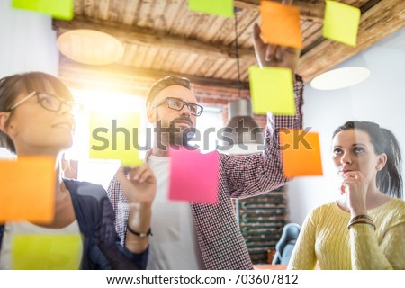 Business people meeting at office and use post it notes to share idea. Brainstorming concept. Sticky note on glass wall. Royalty-Free Stock Photo #703607812