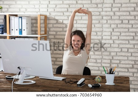 Happy Young Businesswoman Stretching Her Arms At Workplace #703654960