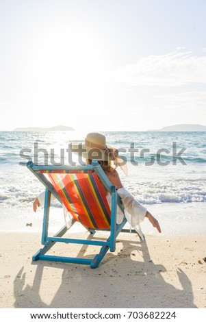 Travel vacation woman relaxing  on sun bed sofa lounge chair on holidays at the tropical beach #703682224