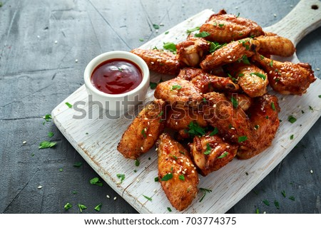 Baked chicken wings with sesame seeds and sweet chili sauce on white wooden board. Royalty-Free Stock Photo #703774375