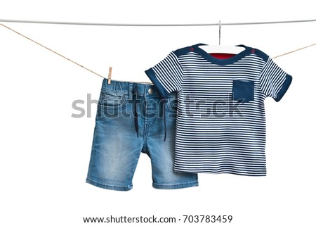 Fashion denim baby-boy shorts and T-shirt (marine style) hanging on a rope isolated on white background/ Baby clothes/ Close-up.  #703783459