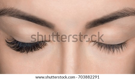 Eyelash removal procedure close up. Beautiful Woman with long lashes in a beauty salon. Eyelash extension. Royalty-Free Stock Photo #703882291