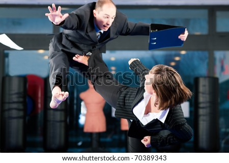 Business concept - People in a gym in martial arts training exercising Taekwondo, both wearing suits #70389343